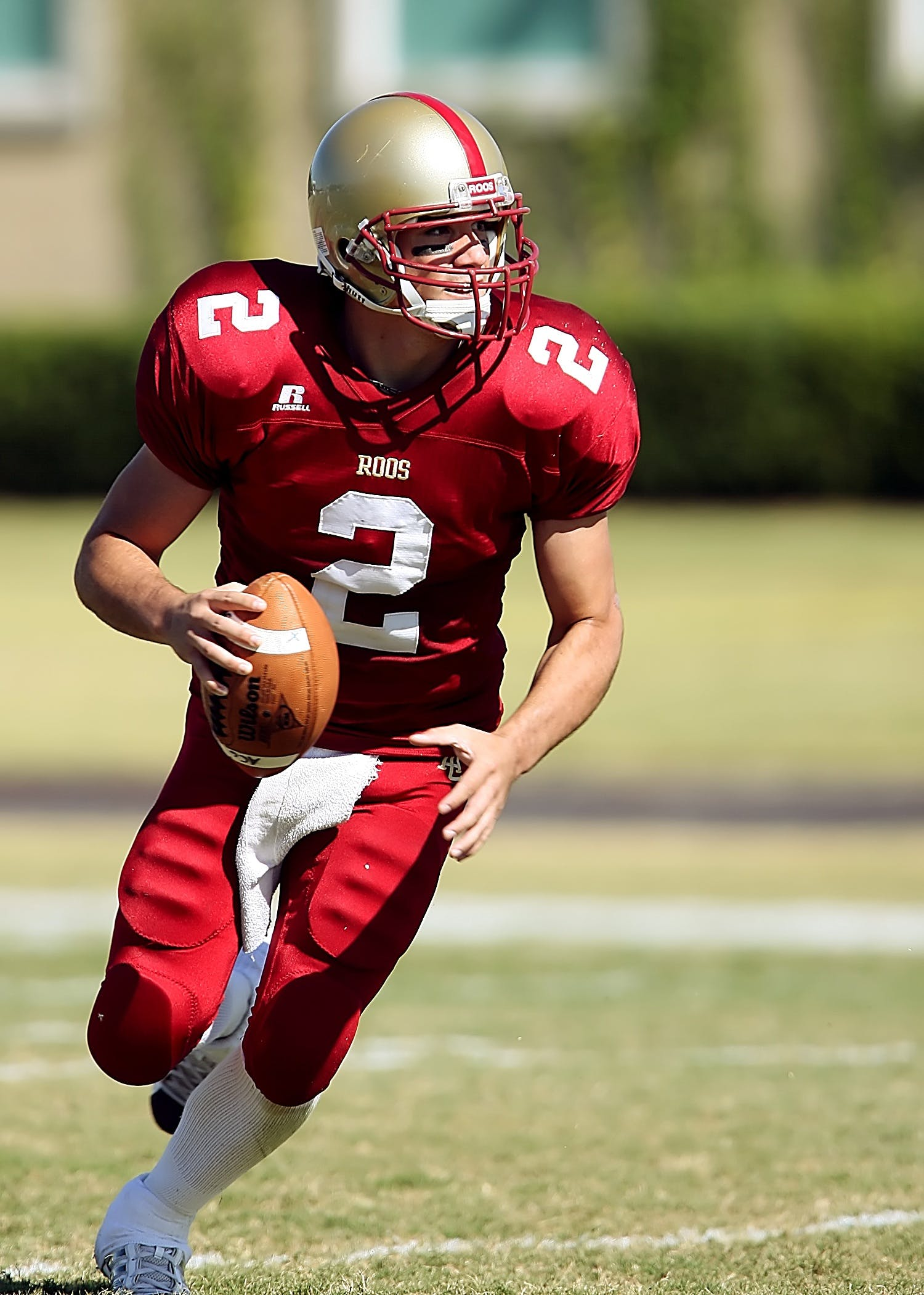 Football Player With Ball Running on Green Field during Daytime