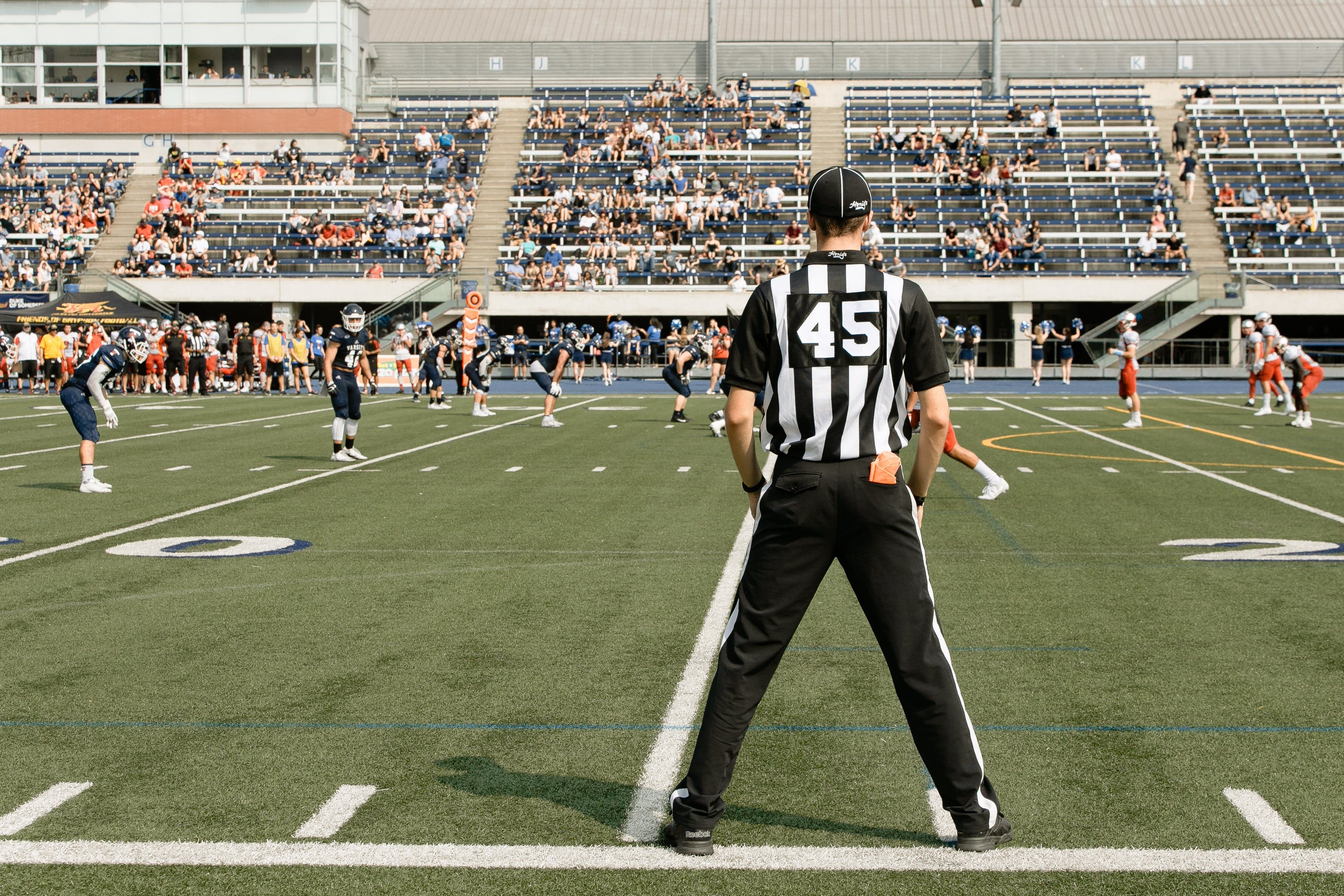 Man in Black and White Jersey Shirt and Black Pants Standing on Football Field